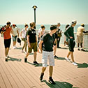 A group of pedestrians turning in curiosity on the Coney Island Boardwalk, New York City